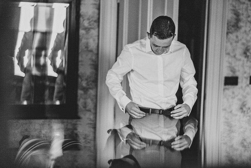 groom is putting on his belt