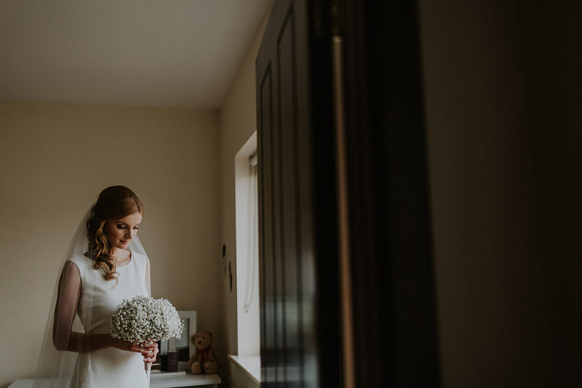 portrait of the bride at the window inside the house before curch ceremony