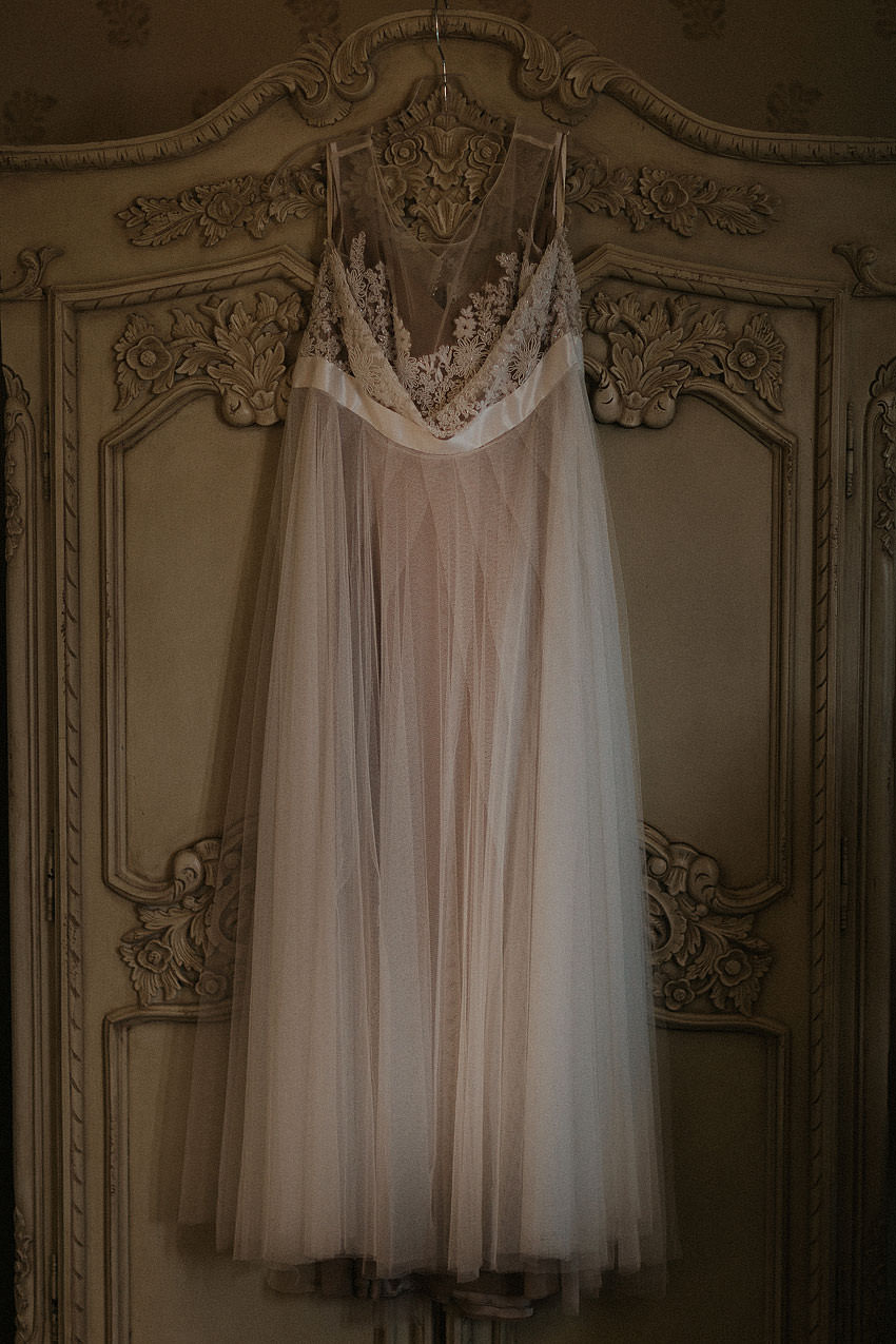 fairy style wedding dress hanging on the old wardrobe