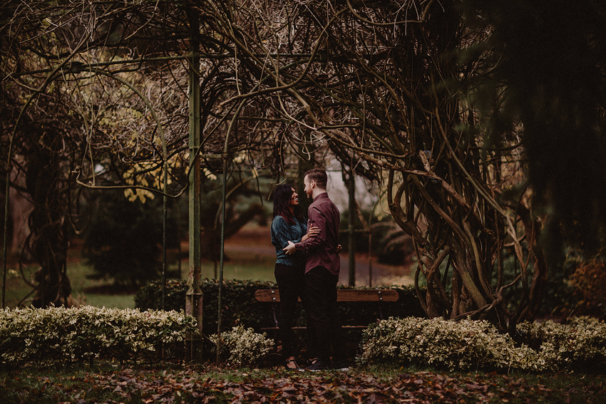 couple standing face to face under the tree in botanic gardens