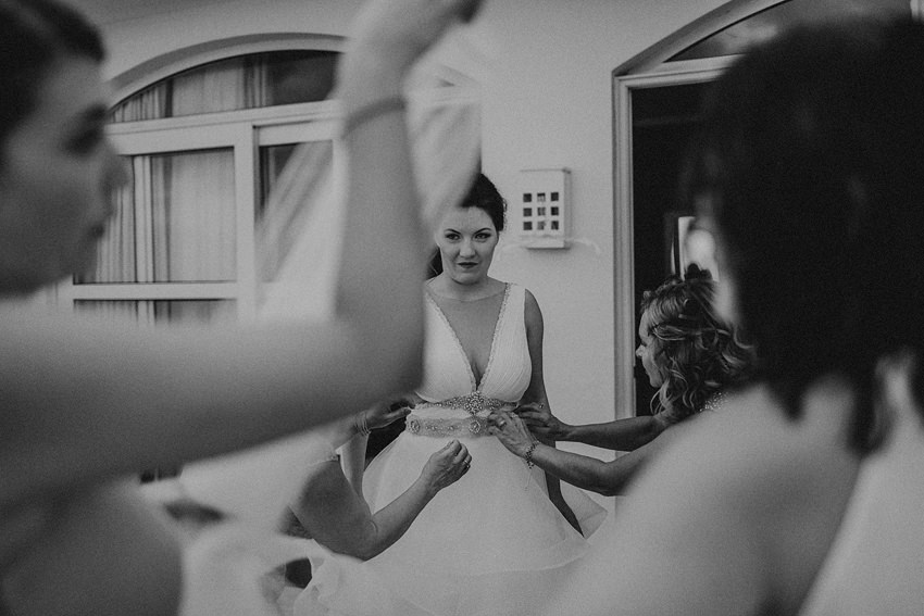 girls helping Elena to put the dress on