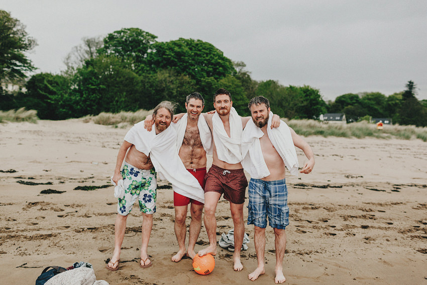 groom and groomsmen playing football on Rathmullan beach