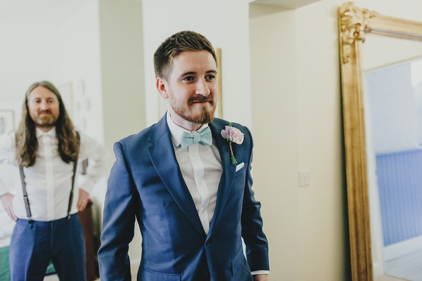 groom looking in the mirror ready to leave to the church, wearing blue suits and bright blue bow tie