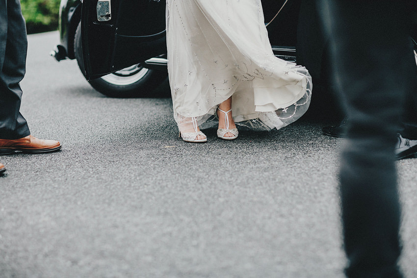 Bride is walking out the car, waering gorgeous Emmy London shoes