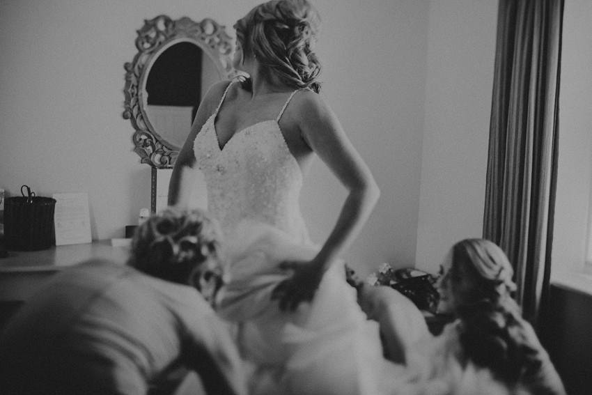 gorgeous photo of Rachel and her brides halping her with putting stunning dress on