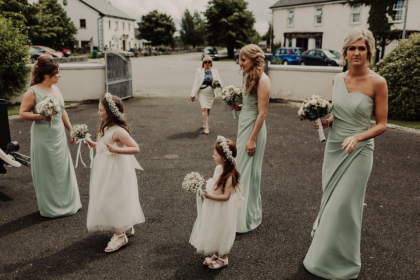 Bridesmaids and flower girls waiting for the bride in front of the church