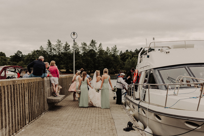 bridal party is taking a boat to get to the drinks reception