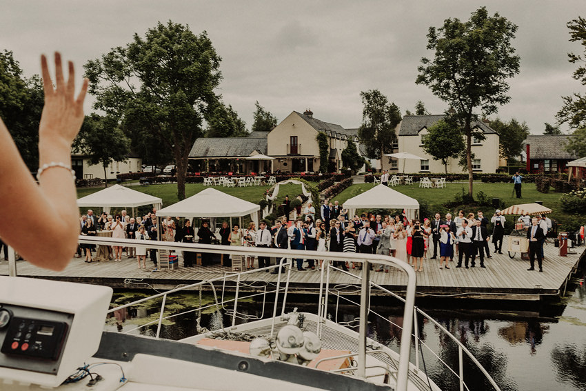 Bride is waving hand to the all guests from the boat