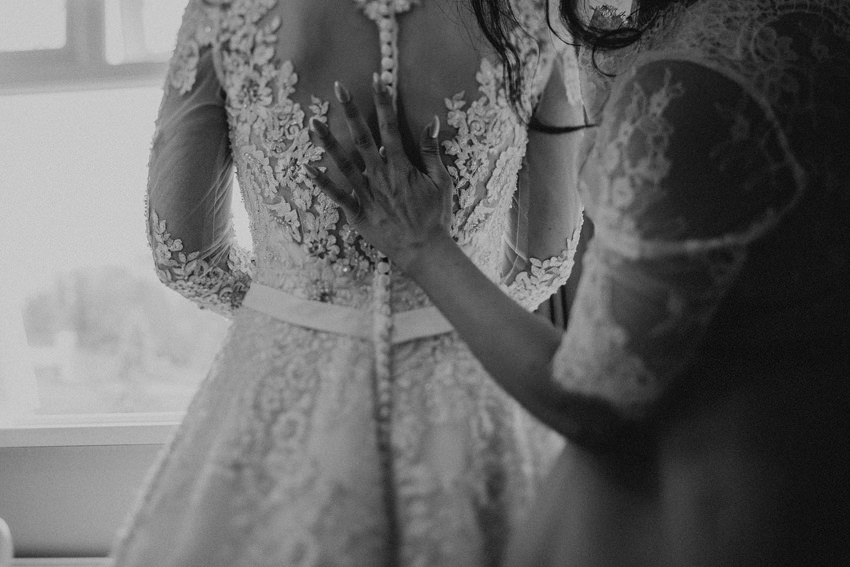 sister of the bride is checking all the buttons on the back of the dress
