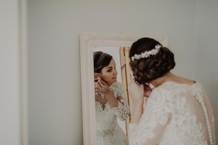 bride is putting her earrings, reflection in the mirror