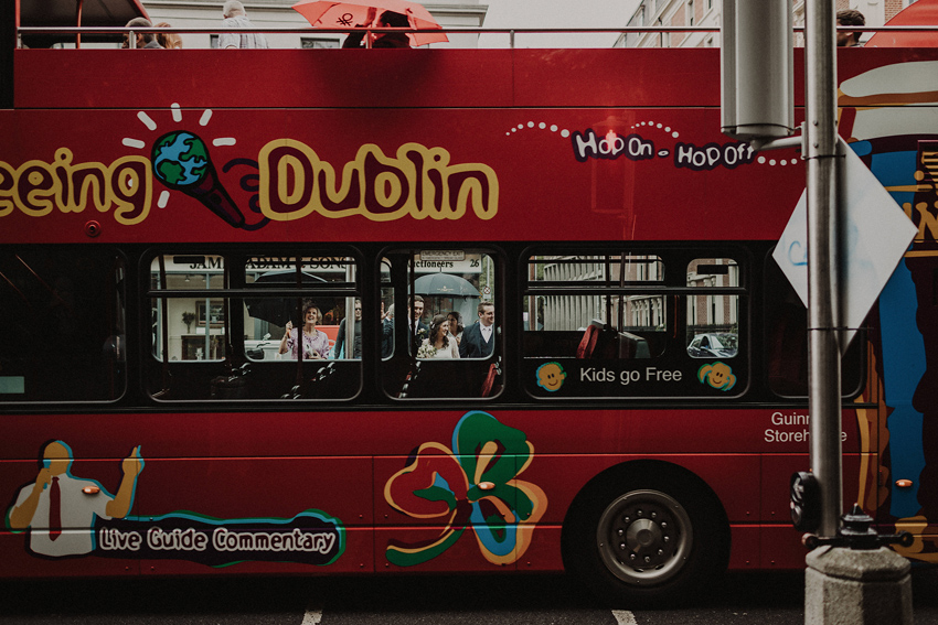 cool shot of bride and groom through the dublin sightseeing bus