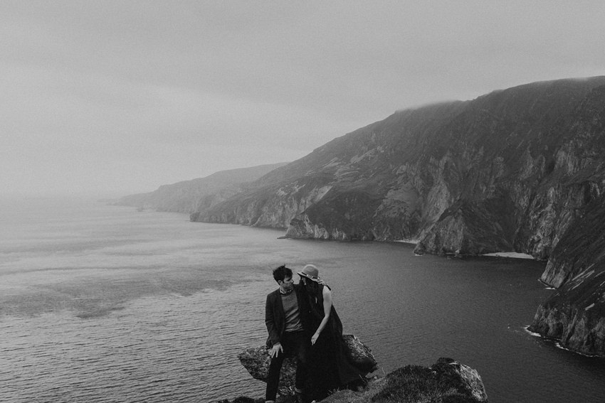 Nile and Maggie are sitting on the rock with the view on slieve league the highest cliffs in ireland behind their backs