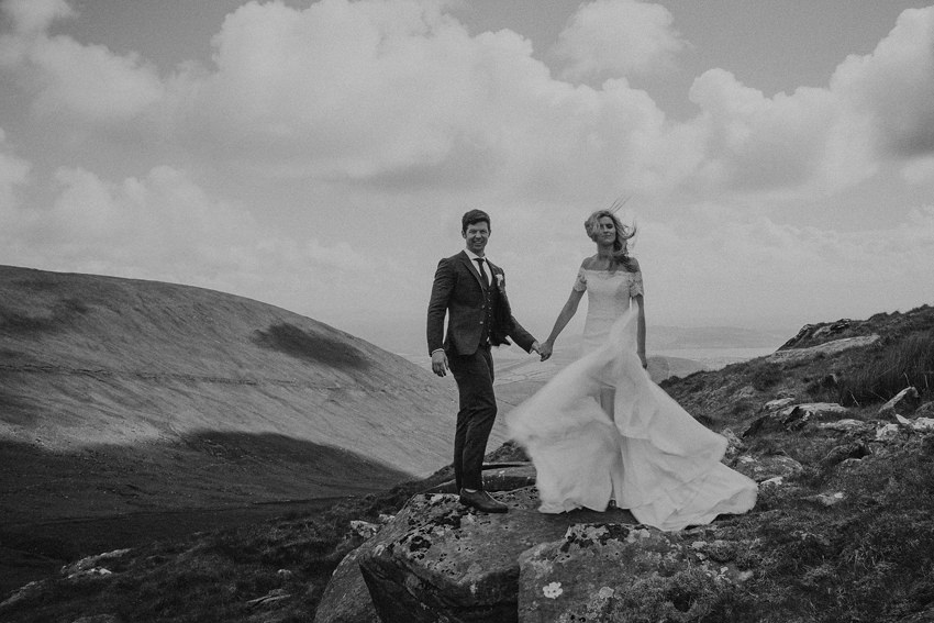 epic photo on the mountain with movement in the wedding dress