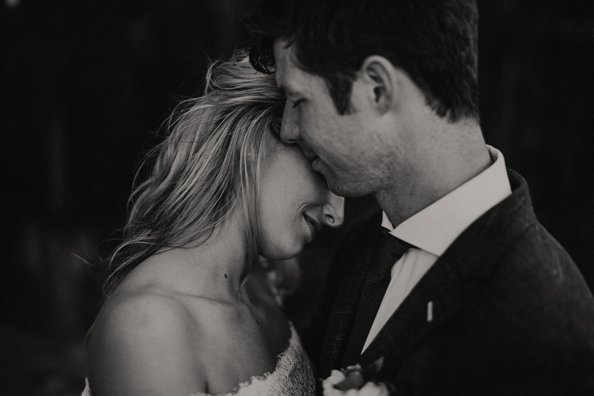 black and white photo groom is touching brides cheek with his lips
